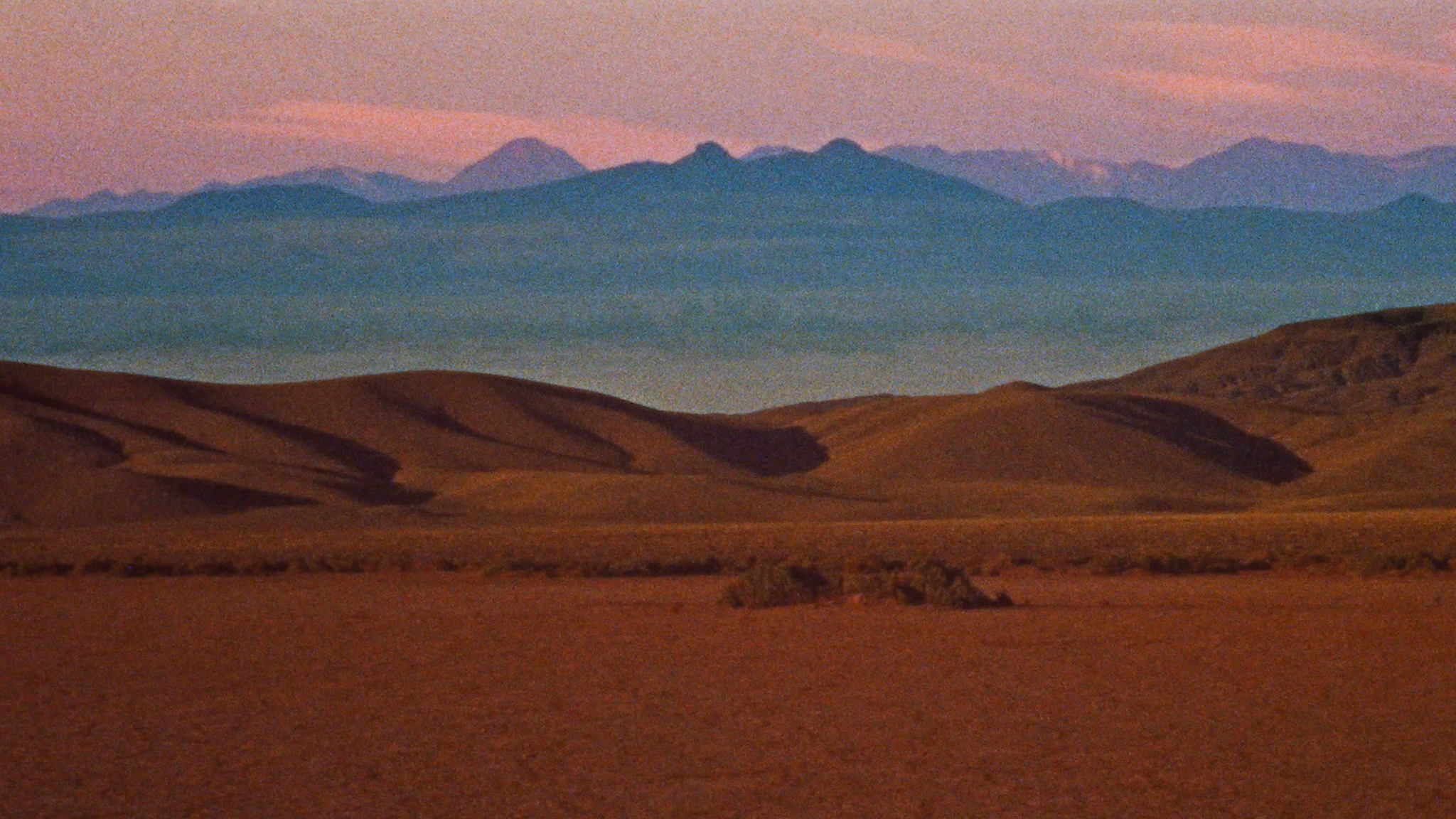 Landscape image of mountains with blue/purple tones in the background and red tones in the foreground