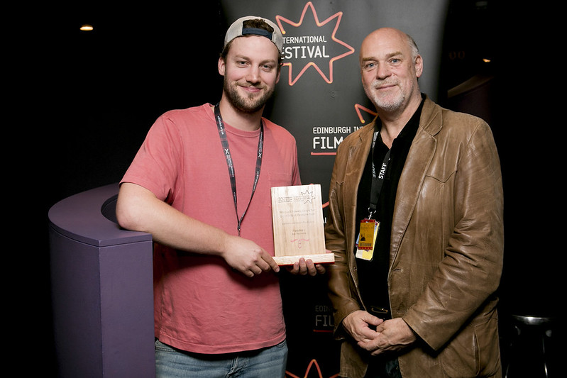 Ben Sharrock and EIFF Artistic Director Mark Adams pose with Ben's Michael Powell Award for Pikadero in 2016