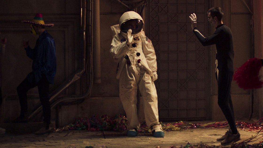 Still from Apples, a man in a spacesuit walks through a warehouse-like room. A man in a skeleton costume waves and someone wearing a sombrero stands in the background.