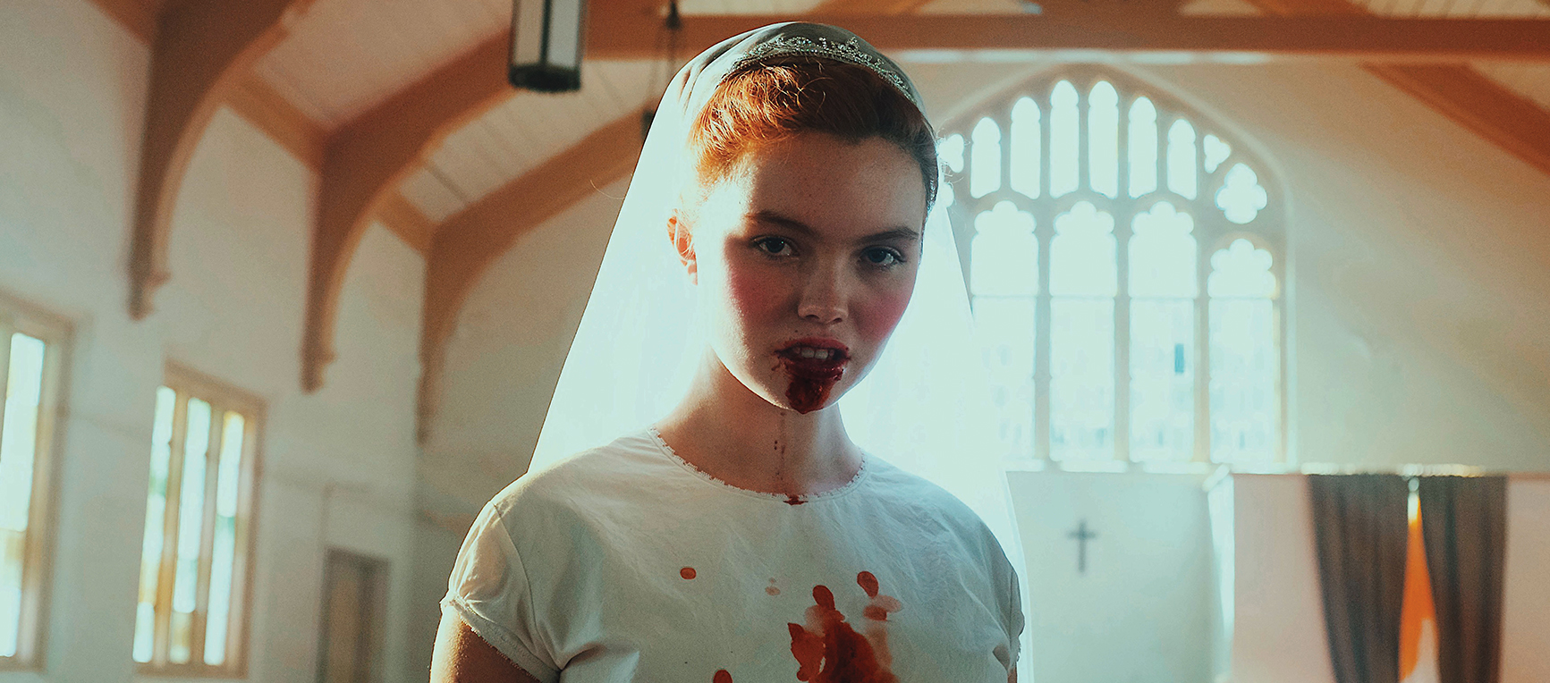 Darlin':A young women dressed as a bride drips blood from her mouth.