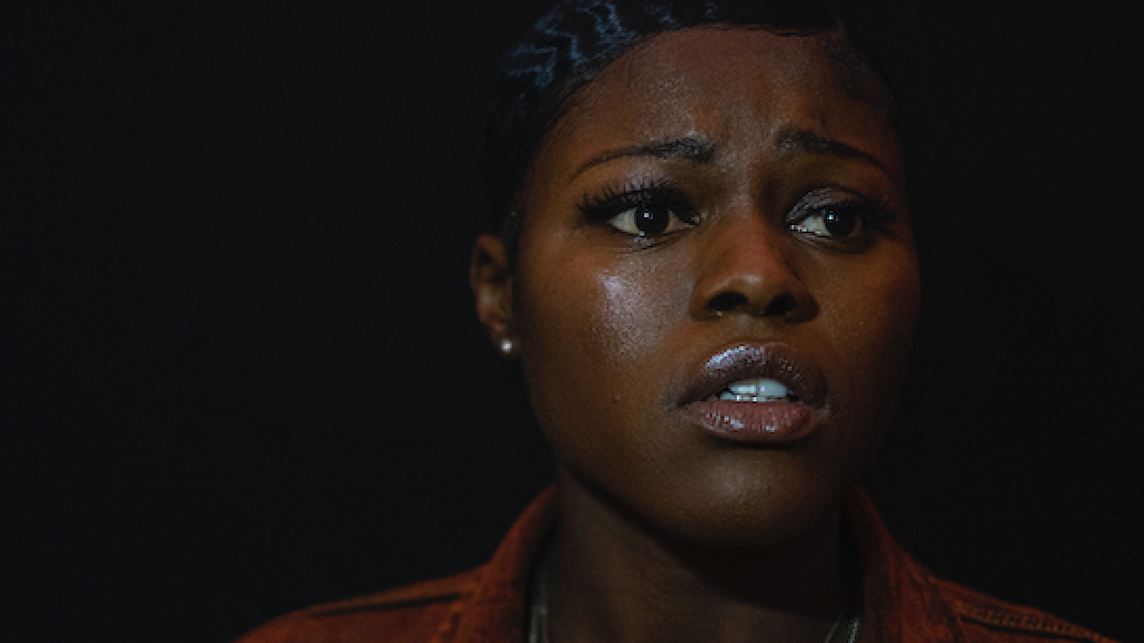 Still from Expensive Shit, Tolu, a Black woman, stares off into the distance in fear and shock