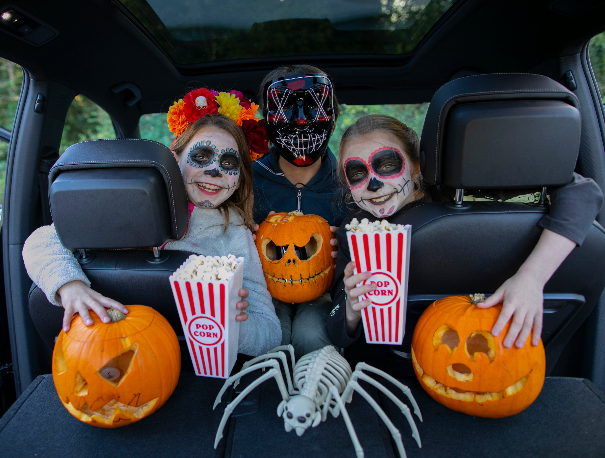 Two girls sit in the car looking through the headrests, wearing Day of the Dead make-up. A masked parent sits between them spookily! They are surrounded by three pumpkins, the middle one is glowing and they hold a box of popcorn each. A large spider poses next to the pumpkins.