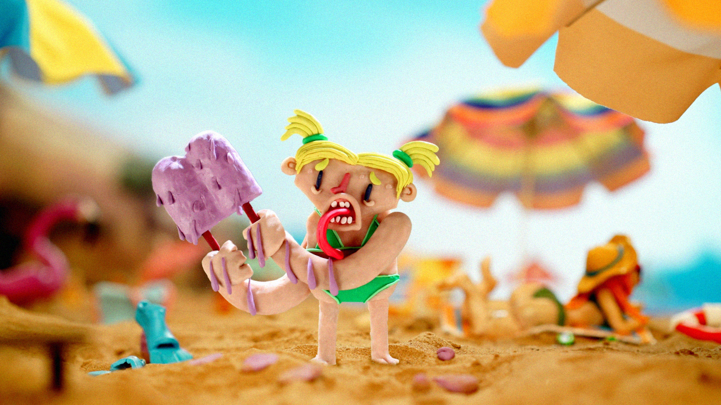 Heatwave: a claymation figure of a small girl licks an ice lolly on a beach.