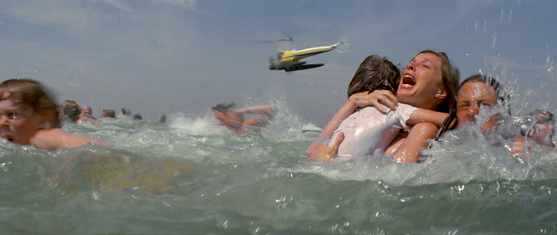 Crowds panic to leave the water including a mother clutching her small child. A yellow helicopter flies overhead.