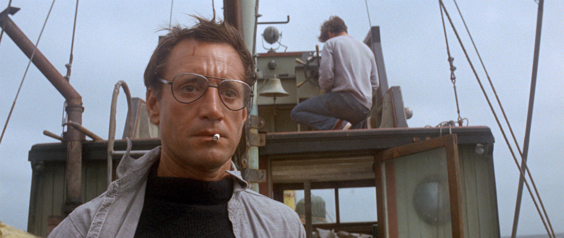 Brody looks out to the ocean and smokes a cigarette on board the Orca, while Quint steers the boat in the background