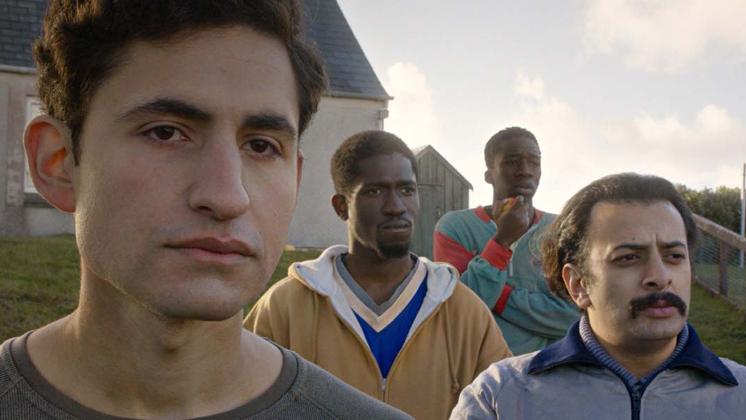 Still from Limbo, Omar, Farhad, Wasef and Abedi stand looking past the camera. They are four refugees stuck on a remote Scottish island.