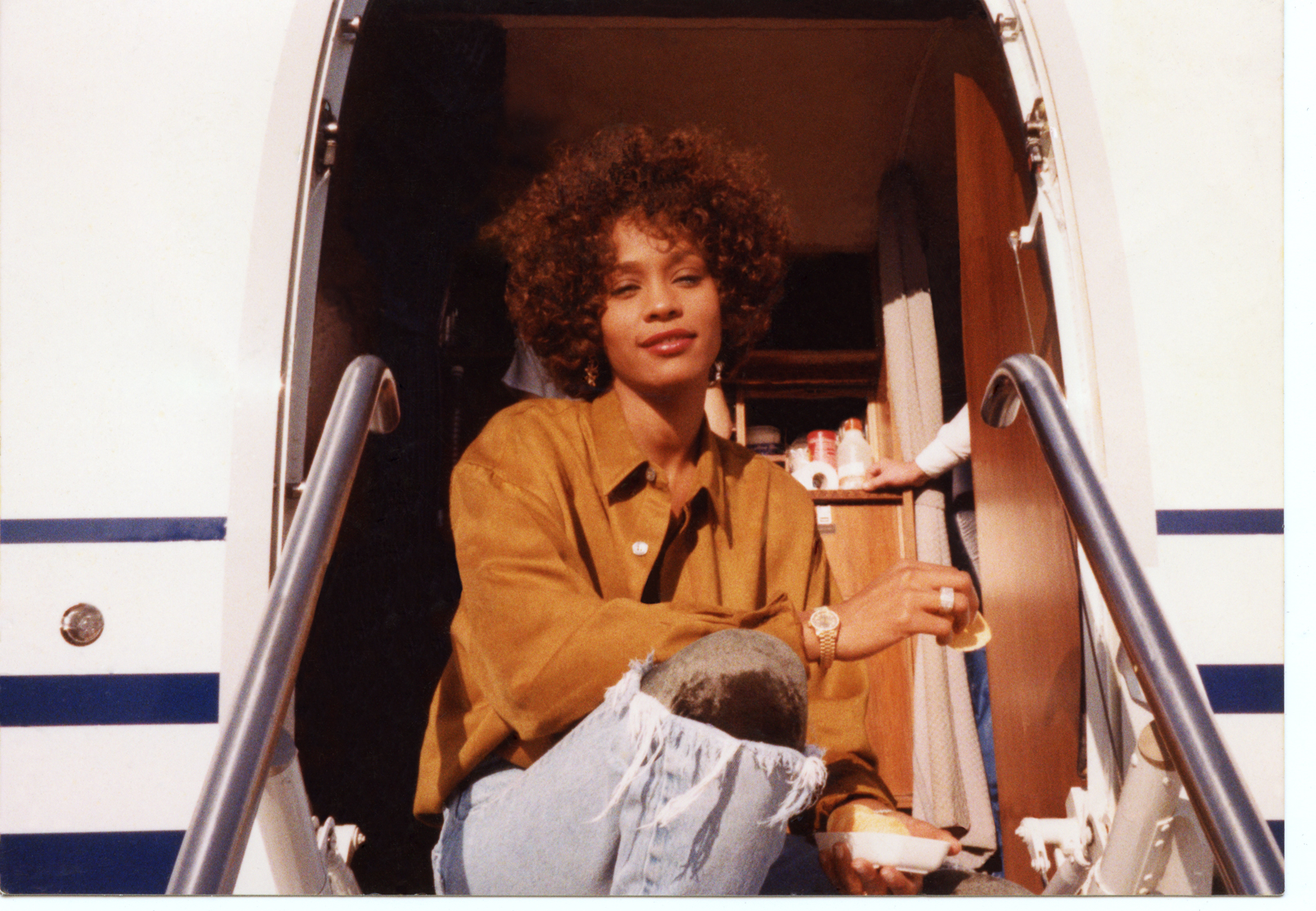 Whitney Houston sits in the entrance to her private jet